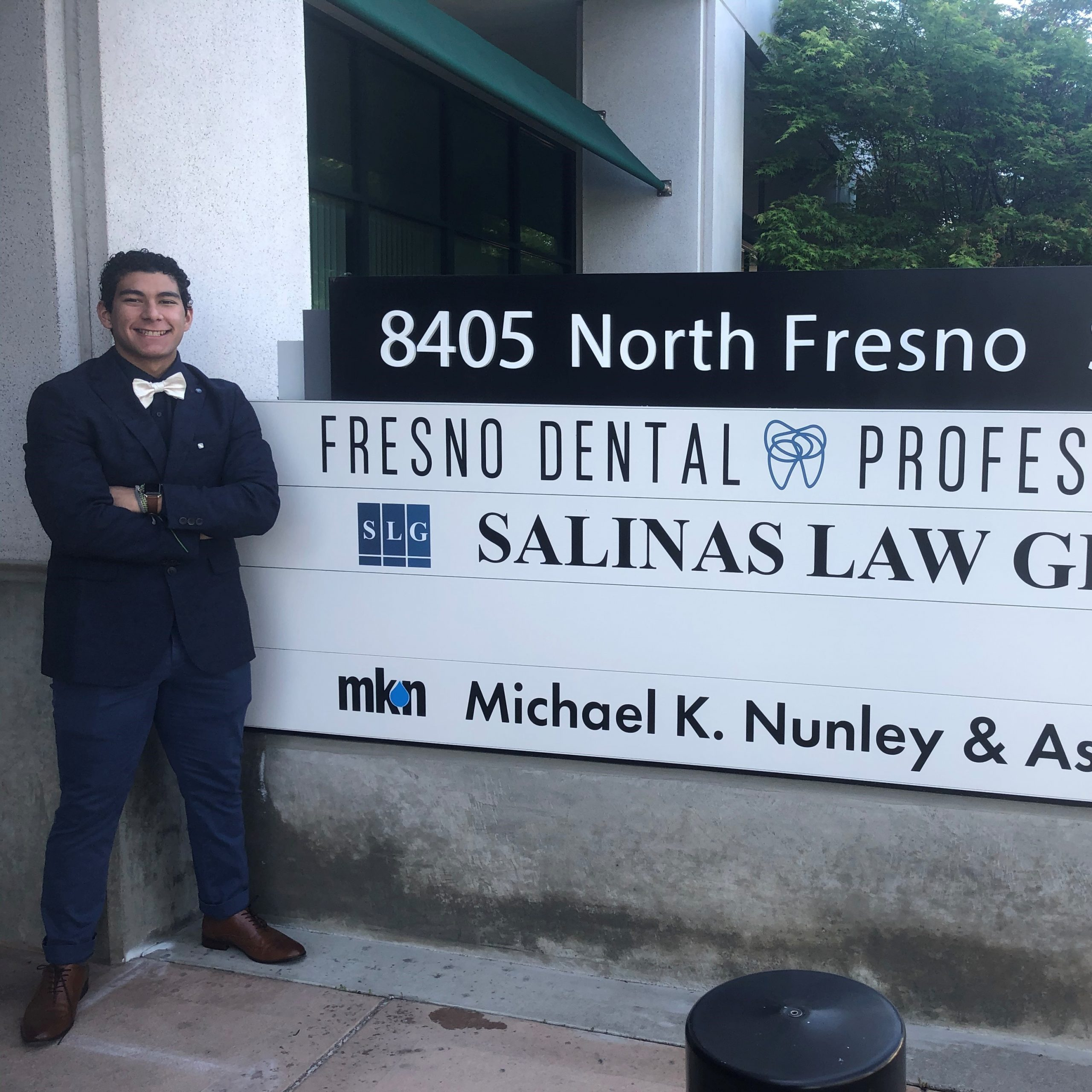 Xavier Vera standing next to the MKN Fresno office's building sign
